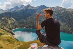 El hombre joven asentado en una roca en las montañas come la sandía y la mirada al panorama imagen de archivo