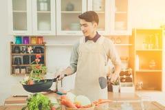 El hombre joven asiático está cocinando Imagen de archivo