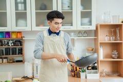 El hombre joven asiático está cocinando Imagen de archivo libre de regalías