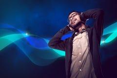 El hombre joven asiático escucha la música vía el auricular Fotografía de archivo
