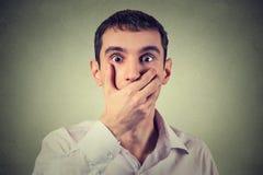 El hombre joven asustado con entrega su boca, pasmado y mudo Imagen de archivo libre de regalías
