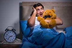 El hombre joven asustado en cama Foto de archivo libre de regalías