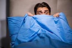 El hombre joven asustado en cama Imágenes de archivo libres de regalías