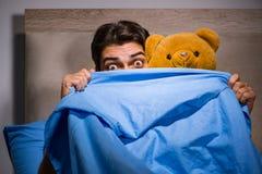 El hombre joven asustado en cama Imagen de archivo libre de regalías