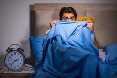 El hombre joven asustado en cama Foto de archivo
