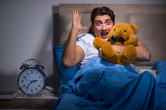 El hombre joven asustado en cama Fotos de archivo libres de regalías