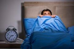 El hombre joven asustado en cama Imagenes de archivo