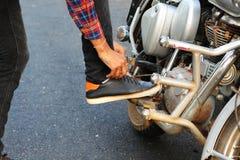 El hombre joven ata su zapato en la bici imagen de archivo libre de regalías