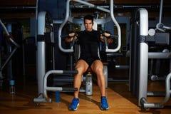 El hombre joven atlético que dobla el pecho muscles en la máquina de la prensa imágenes de archivo libres de regalías