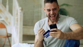 El hombre joven atractivo con compras de la tarjeta del smartphone y de crédito en Internet se sienta en cama en casa imagen de archivo libre de regalías