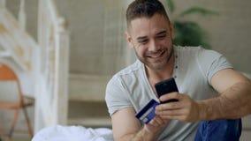 El hombre joven atractivo con compras de la tarjeta del smartphone y de crédito en Internet se sienta en cama en casa almacen de metraje de vídeo