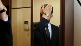 El hombre joven atractivo en un traje y un lazo endereza su situación del pelo delante del espejo en el vestíbulo 4K v?deo 4K almacen de video