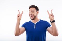 El hombre joven atractivo está gesticulando feliz y Imágenes de archivo libres de regalías