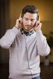 El hombre joven atractivo que escuchaba la música en los auriculares, ojos se cerró Imagen de archivo libre de regalías
