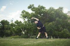 El hombre joven atractivo que hace estirar ejercita con las manos al aire libre en parque fotografía de archivo libre de regalías