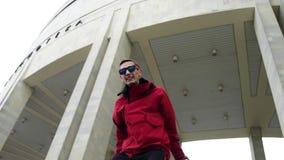 El hombre joven atractivo que lleva la chaqueta y las gafas de sol rojas golpea activamente en la calle almacen de video