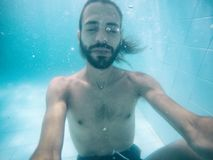 El hombre joven atractivo se sumergió en piscina con los ojos cerrados fotografía de archivo