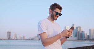 El hombre joven atractivo y hermoso con la sonrisa hermosa y la generaci?n milenaria z del inconformista mira, enrolla con social metrajes