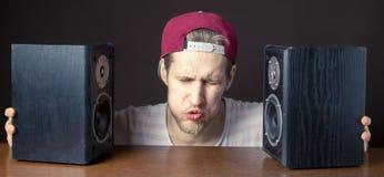 El hombre joven audiófilo escucha la música ruidosa de los altavoces f imagen de archivo libre de regalías