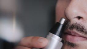 El hombre joven barbudo afeita su nariz con un condensador de ajuste almacen de video