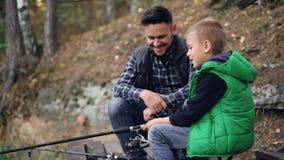 El hombre joven barbudo está pescando con el niño lindo el día del otoño, el muchacho está sosteniendo la barra y está hablando c metrajes