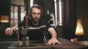 El hombre joven, barbudo, hace las mercancías de cuero almacen de video