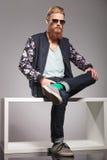 El hombre joven barbudo se sienta en la pequeña tabla Imagen de archivo