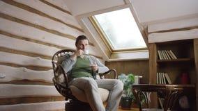 El hombre joven bebe el café en el ático almacen de metraje de vídeo