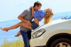 El hombre joven besa a la mujer que se sienta en coche contra el mar Fotos de archivo libres de regalías