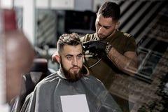 El hombre joven brutal con la barba se sienta en una peluquería de caballeros El peluquero en guantes negros afeita los pelos en  fotografía de archivo