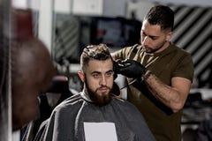 El hombre joven brutal con la barba se sienta en una peluquería de caballeros El peluquero en guantes negros afeita los pelos en  imagen de archivo