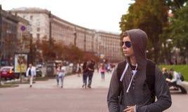 El hombre joven camina abajo de la calle de una ciudad grande Foto de archivo