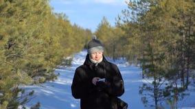 El hombre joven camina a lo largo de la trayectoria de bosque y empuja su finger en el teléfono móvil almacen de video