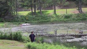 El hombre joven camina a lo largo de un lago almacen de video