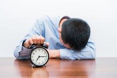 El hombre joven cansado presionó el despertador imagenes de archivo