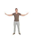 El hombre joven casual que miraba para arriba con los brazos extendió Imagen de archivo libre de regalías