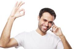 el hombre joven casual que muestra los pulgares sube la muestra Imágenes de archivo libres de regalías