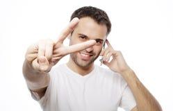 el hombre joven casual que muestra los pulgares sube la muestra Imagen de archivo libre de regalías