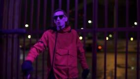 El hombre joven caucásico en chaqueta y gafas de sol rojas enérgico canta por la tarde metrajes