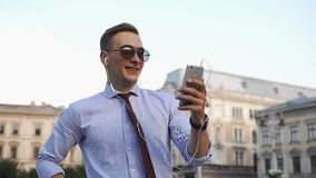 El hombre joven comprueba su teléfono que se coloca en la calle almacen de video