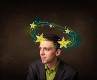 El hombre joven con amarillo protagoniza circleing alrededor de su cabeza Fotografía de archivo libre de regalías