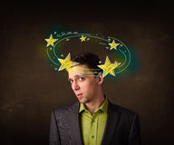 El hombre joven con amarillo protagoniza circleing alrededor de su cabeza Imagen de archivo