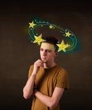 El hombre joven con amarillo protagoniza circleing alrededor de su cabeza Imágenes de archivo libres de regalías