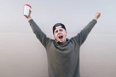 El hombre joven con café en las manos de la felicidad levantó sus manos hacia arriba contra la perspectiva de una pared ligera Imagen de archivo