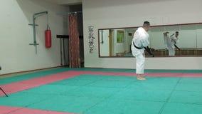 El hombre joven con el cuerpo musculoso, artes marciales de entrenamiento Goju-Ryu Karate-hace cámara lenta estupenda almacen de metraje de vídeo