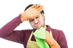 El hombre joven con el delantal y los guantes cansaron para limpiar Fotos de archivo libres de regalías
