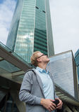 El hombre joven con el pelo rubio, los vidrios que llevan mira para arriba los edificios altos del centro de negocios Foto de archivo libre de regalías
