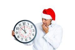 El hombre joven con el sombrero de Navidad se preocupó de tiempo Fotografía de archivo