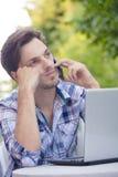 El hombre joven con el teléfono escucha alguien el agujerear al aire libre imagenes de archivo