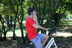El hombre joven con hablar del smartphone se sienta en la bici en madera imagenes de archivo